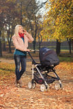 一个电话的年轻母亲在与她的婴孩的步行期间 库存照片