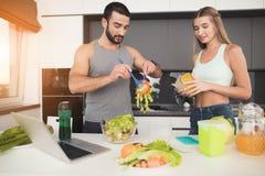 一个男人和一名妇女在厨房里早晨 人计划在船上的沙拉 免版税库存图片
