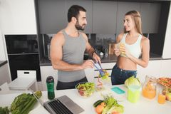 一个男人和一名妇女在厨房里早晨 人计划在船上的沙拉 免版税库存照片