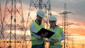 一个男人和一名妇女有膝上型计算机的在输电线塔旁边工作 工作在可再造能源发展的工程师 股票录像