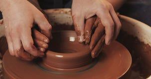 一个男人和一名妇女的手黏土的在横式转盘模子花瓶 陶瓷工在有黏土的瓦器车间工作 影视素材