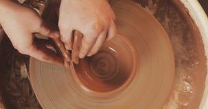 一个男人和一名妇女的手黏土的在横式转盘模子花瓶 陶瓷工在有黏土的瓦器车间工作 股票录像