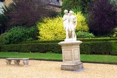 一个男人和一名妇女的雕象柱基的和一个位子在庭院里 库存图片