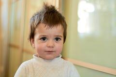 一个男婴的特写镜头室内画象有淘气头发的 孩子的各种各样的情感 图库摄影