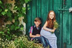 一个男孩和一个女孩从老门 库存图片