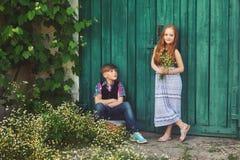 一个男孩和一个女孩从老门 免版税图库摄影