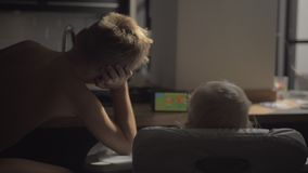 一个男孩和一部女婴观看的动画片的后面看法在片剂 股票录像