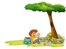一个男孩和他的猫在树下 库存照片