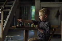 一个男孩在一个老房子下棋 库存图片