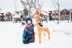 一个男孩在为圣诞节装饰的一个冬天村庄围场 免版税库存照片