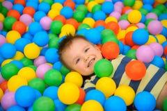 一个男孩在有许多一点色的球的使用的屋子 库存图片
