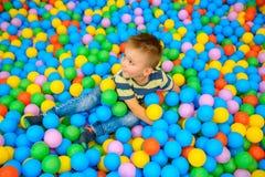 一个男孩在有许多一点色的球的使用的屋子 库存照片