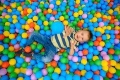 一个男孩在有许多一点色的球的使用的屋子 免版税库存照片