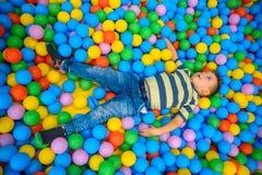 一个男孩在有许多一点色的球的使用的屋子 免版税库存图片