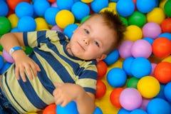 一个男孩在有许多一点色的球的使用的屋子 图库摄影