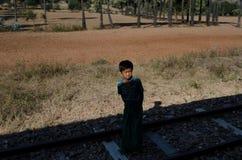 一个男孩在缅甸看往从阴影的一列火车 免版税图库摄影