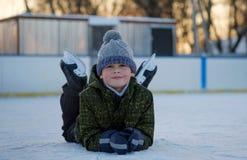 一个男孩室外滑冰场的画象在冬天 免版税库存图片