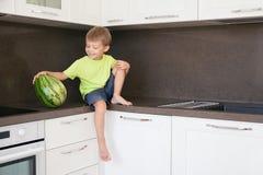 一个男孩用一个西瓜在厨房里 免版税图库摄影