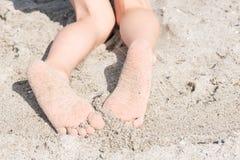 一个男孩的两英尺沙子的在海滩 免版税图库摄影