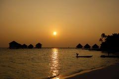 一个男孩的剪影一条小船、平房和棕榈的在日落 免版税图库摄影