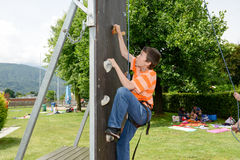 一个男孩的努力攀登的墙壁 库存照片