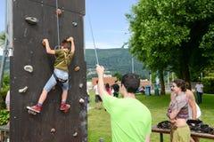 一个男孩的努力攀登的墙壁 库存图片
