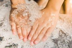一个男孩的手有水飞溅的,由后照在平衡的su 免版税图库摄影