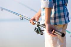 一个男孩的手特写镜头有一根钓鱼竿的 免版税库存图片