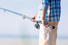 一个男孩的手特写镜头有一根钓鱼竿的 免版税图库摄影