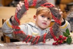 一个男孩的画象有用红色小珠装饰的圣诞节花圈的 免版税图库摄影