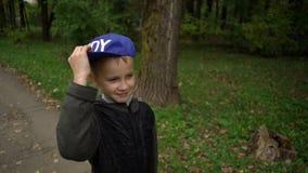 一个男孩的画象有pennyboard的 欧洲出现的人在他的手和微笑上拿着一个便士板 秋天 股票视频