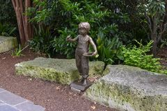 一个男孩的铜雕塑有一只鸟的在他的由加利价格的手上在达拉斯树木园和植物园 免版税库存照片