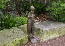 一个男孩的铜雕塑有一只鸟的在他的由加利价格的手上在达拉斯树木园和植物园 库存照片