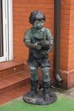 一个男孩的雕塑有一只鸟的在砖buildi附近的手上 免版税库存照片