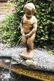 一个男孩的雕象在庭院里 库存照片