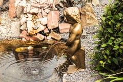 一个男孩的雕象在庭院里 免版税图库摄影