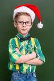 一个男孩的画象圣诞节盖帽的在校务委员会附近 图库摄影