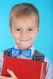 一个男孩的画象拿着红色书的校服的 图库摄影