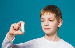 一个男孩的画象拿着药片的白色衣裳的 免版税图库摄影