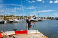 一个男孩的画象码头的有被停泊的航行的乘快艇 库存图片