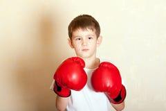 一个男孩的画象红色拳击手套的 库存照片