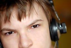 一个男孩的画象耳机的 库存图片