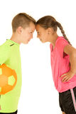 一个男孩&女孩的滑稽的画象倾斜接触的足球制服的 免版税库存照片