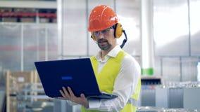 一个男性工厂劳工的运作的过程保护工作服的与膝上型计算机 股票视频