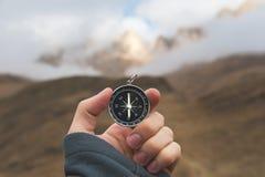 一个男性徒步旅行者寻找与一个磁性指南针的一个方向在秋天的山 观点射击 人` s 免版税库存图片
