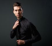 一个男性时装模特儿的画象在黑衬衣和领带的 图库摄影