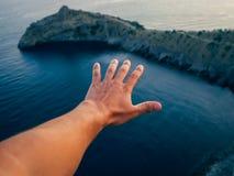 一个男性游人的手本质上在蓝色海背景的 免版税库存照片