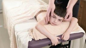 一个男性生理治疗师男按摩师做裂缝合拢放松的按摩给说谎一个小微笑的男孩在按摩床 题头 股票录像