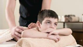 一个男性生理治疗师男按摩师做裂缝合拢放松的按摩给说谎一个的小男孩在按摩床 肩膀和 股票视频