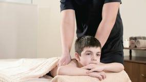 一个男性生理治疗师男按摩师做裂缝合拢放松的按摩给说谎一个的小男孩在按摩床 com递 股票视频